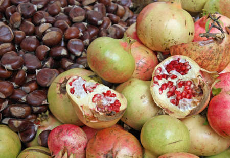 classic autumn fruits with many ripe chestnuts and pomegranates photo