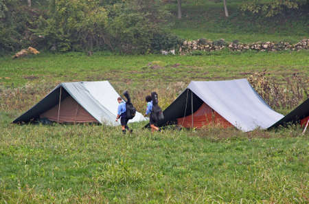 two Italian boy scouts with blue uniforms walking amidst the camping tents