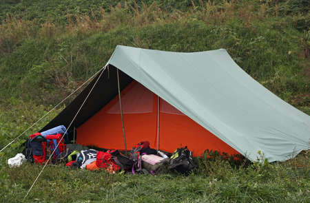 Orange tent with many backpacks deposited in front of the entrance Stock Photo