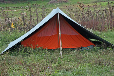 Orange tent with green roof mounted on a hillside meadow