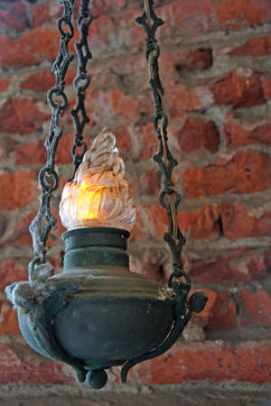 votive: hanging votive antique lamp with red brick wall Stock Photo