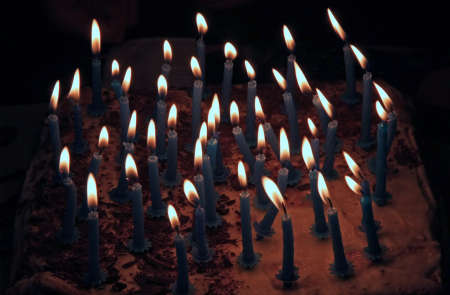 lots of lighted candles on a cake with cream for the birthday party Imagens