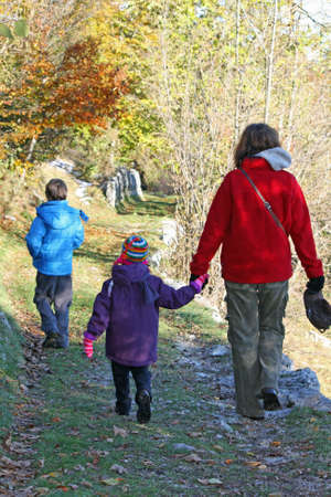 family with MOM and two children walking on the path in autumn Stock Photo - 16293566