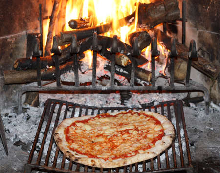 tasty pizza margherita baked in to the fire of a fireplace in the tavern photo
