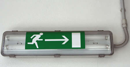 lamp with the emergency exit sign installed within a European factory photo