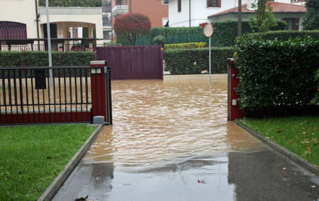 entry of a House during a flood and completely flooded road photo