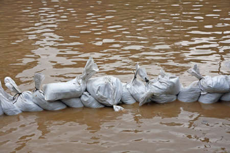 overflows: useless wall of sandbags to fend off raging river Stock Photo