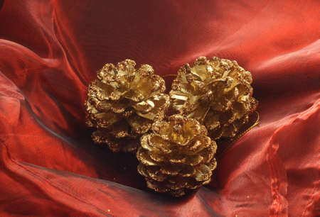 three gilded pine cones as Christmas decoration placed on silk Red photo