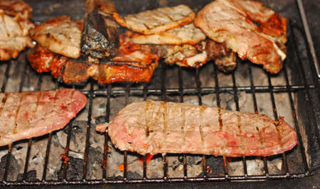 juicy steaks cooked medium rare beef grilled on the barbecue in the garden photo