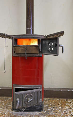 stove pipe: red old wood stove on to heat the ancient villa of Count Stock Photo
