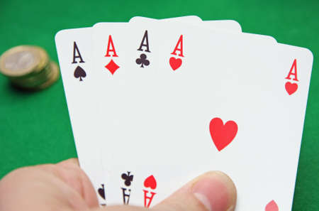hand with poker of aces on a table game photo