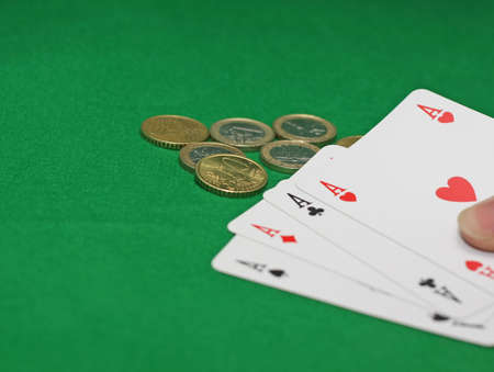 poker d'as avec des pi�ces en euros sur la table de casino vert photo
