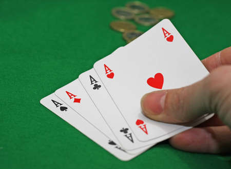 punter: hand with poker of aces on a green table game Stock Photo