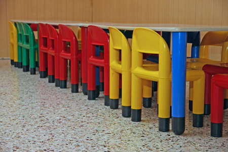 colored plastic chairs and a table in the refectory of the preschool children photo