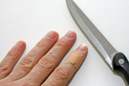 hand with finger with a band aid and the sharp blade of the knife in the kitchen