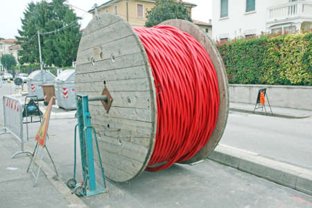 huge coils of red high-voltage power cable in the middle of the road photo