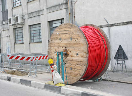 excavation at a construction site during the installation of high-voltage electric cables and large wooden spool photo