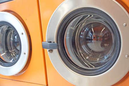 orange automatic washing machines in a laundromat