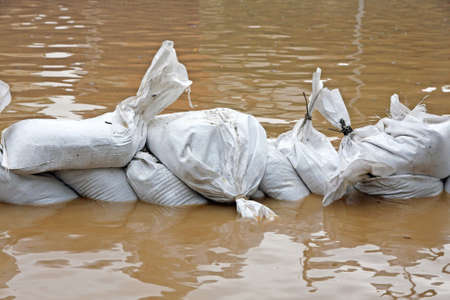 the flood tide: White sandbags for flood defense and brown water Stock Photo