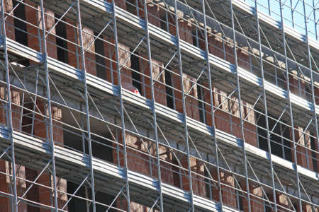 overbuilding: scaffolding during construction of a building on a construction site Stock Photo