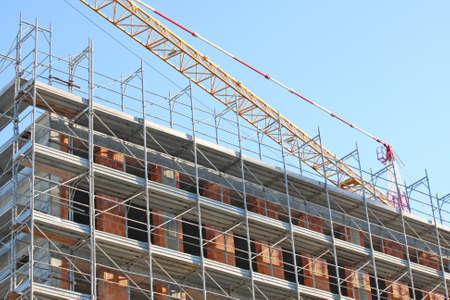 overbuilding: gru e ponteggi durante la costruzione di un edificio in un cantiere edile