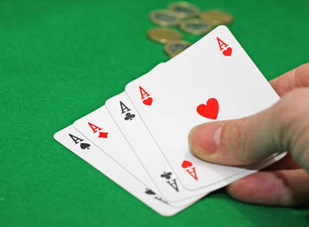 hand with poker of aces on a green table game Stock Photo - 17661121