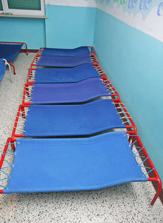 Blue camp beds and little beds for sleeping in a dormitory ofa  nursery school for children Stock Photo - 17661330