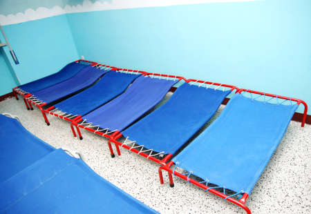 dormitory: Blue camp beds and little beds for sleeping in a dormitory ofa  nursery school for children Stock Photo