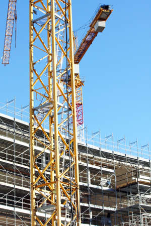 overbuilding: cranes and scaffolding during construction of a building on a construction site