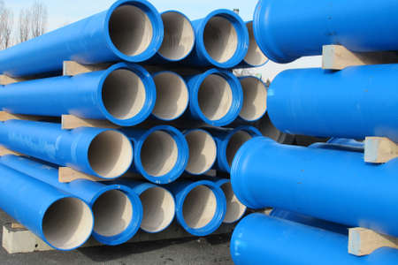 waterworks: piles of concrete blue pipes for transporting water and sewerage