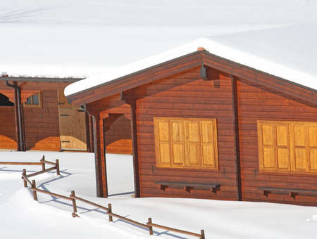 wooden mountain chalet in the Alps in Italy after a heavy snowfall Stock Photo - 17950260