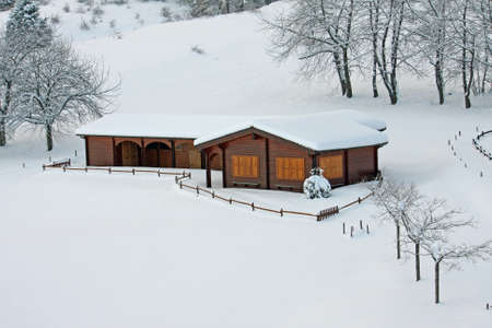 wooden mountain chalet in the Alps in Italy after a heavy snowfall