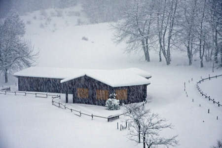 wooden mountain chalet on the Italian Alps during a heavy snowfall Stock Photo - 17950302