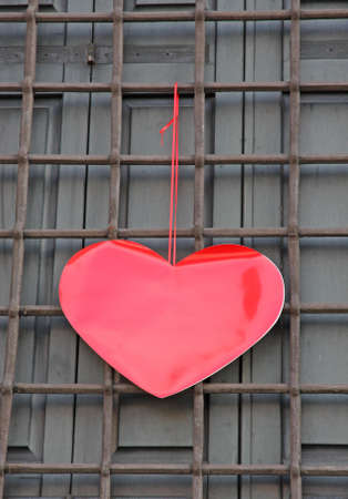 red heart hanging on the grid of a House on Valentine's day photo