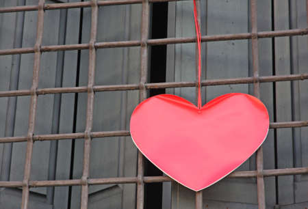 red heart hanging on the grid of a window outside a building on Valentine's day photo