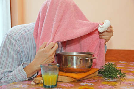 malaise: man with pink towel breathe balsam vapors to treat colds and the flu and a glass of orange juice