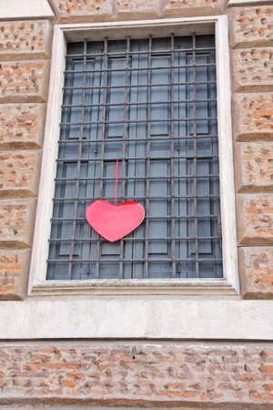 red heart hanging on the grating outside a building on Valentine's day photo