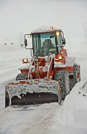 snow plough scraper with the bucket to remove all the snow from the road photo