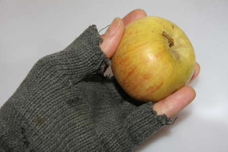 hand of poor man holding an apple just given to him photo