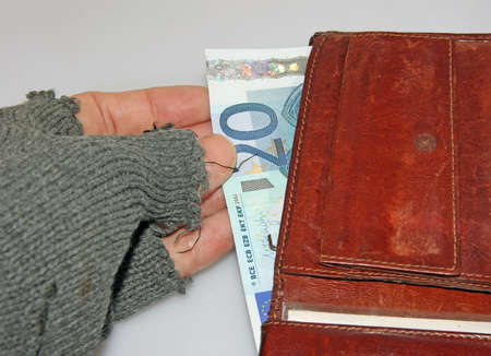marginalized: hand of the poor man who steals euro money from wallet Stock Photo