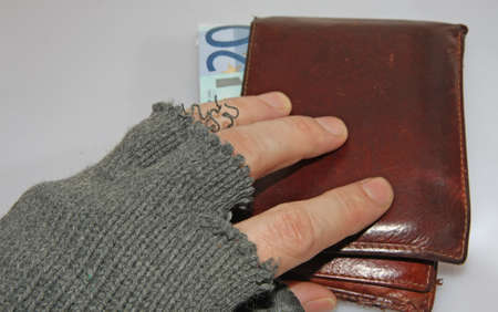 marginalized: hand of the poor man who steals a wallet full of money