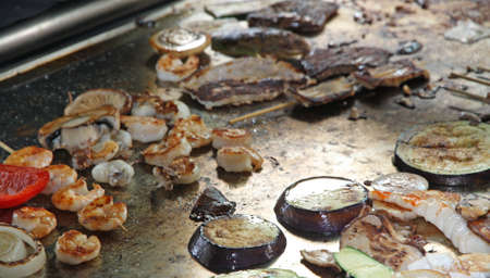 cook griddle: Skewered Shrimp and eggplant cooked vegetables to plate Stock Photo