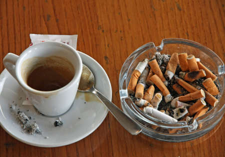 cup of coffee espresso and ashtray chock full of cigarette photo