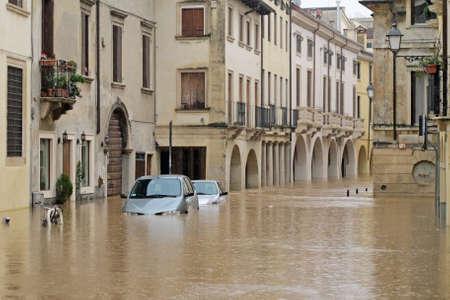 sumergido: los coches en las calles y carreteras sumergidas en el lodo de la inundaci�n despu�s de la inundaci�n del r�o Foto de archivo