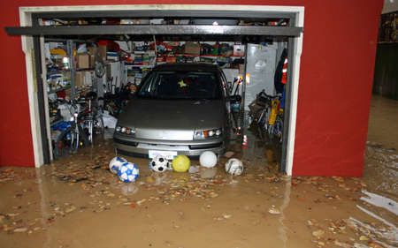 car in the garage of the House submerged by flood mud after the flooding of the River Editorial