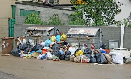 colera: bolsas de los contenedores de basura y desechos en el medio de la carretera llena de barro Editorial