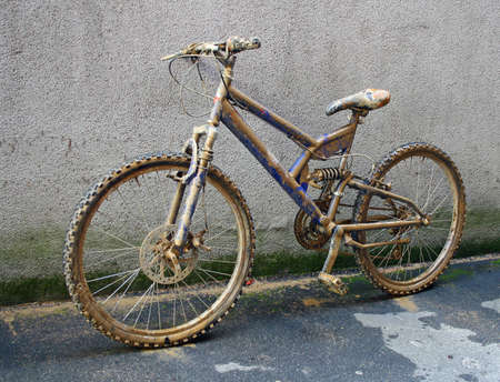 dirtied: climbing bike completely covered with brown mud and sprinkles Stock Photo