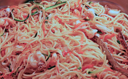 plate of spaghetti topped with vegetables and meat photo