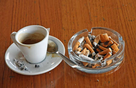 chock: ashtray chock full of cigarette butts and a cup of espresso