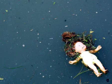 abandoned toy doll on pond water dark photo